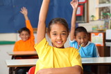 Three primary school children hands raised in class
