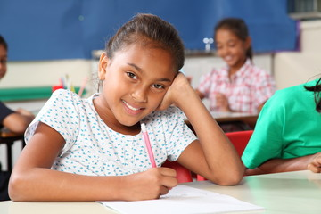 Happy school girl with beautiful smile in class