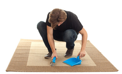 man with sweeping brush and dustpan cleaning carpet