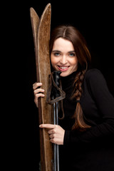 smiling young woman with old wooden skis