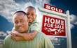 African American Father with Son In Front of Sold Home For Sale