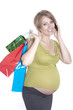 Happy pregnant woman shopping and speaking by phone