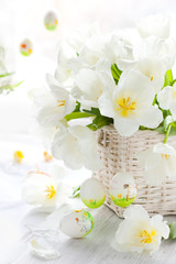 white tulips in a basket and easter colored eggs