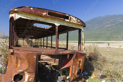 rusty bus wreck in arid landscape