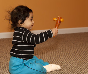 Baby Girl Shaking a Wooden Rattle