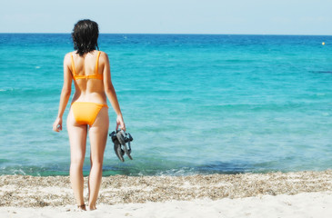 Woman in orange bikini holding flops on the shoreline