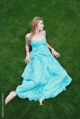 Girl in the blue dress on the green grass