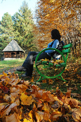 Woman relaxing on bench in a park at Autumn