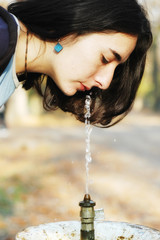 A beautiful girl drinks from a public drinking fountain