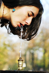 Beautiful girl drinks from a public drinking fountain