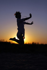 Young woman jumping at the sunset