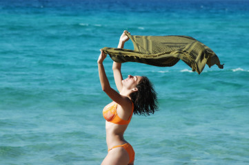 Beautiful  woman on the beach with a colored tissue