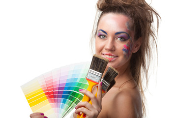 Young woman with a color guide and paintbrushes.