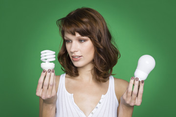 Young woman holding two light bulbs