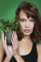 Young woman holding pot of ivy