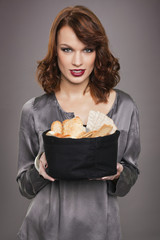 Young woman holding basket of breads