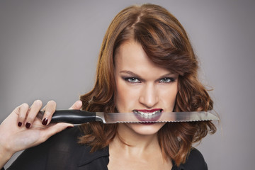 Young woman with knife between teeth