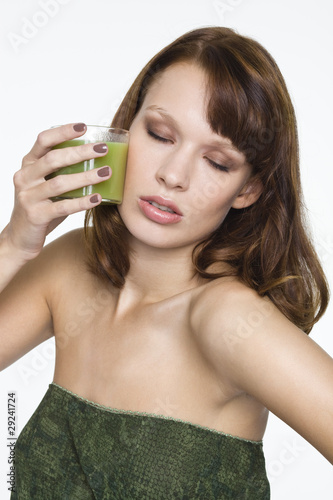 Young woman holding glass of wheatgrass juice