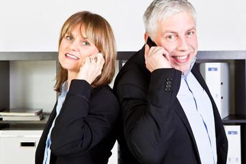 geschäftspartner rücken an rücken beim telefonieren