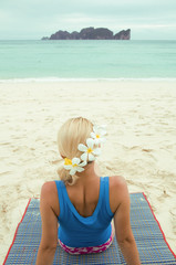 Woman lying on the beach with flowers in her hair