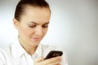 Young woman sending an sms, grey background