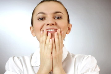 Portrait of a surprised young woman, grey background