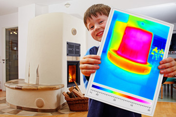 boy showing thermal imaging of a warm masonry stove
