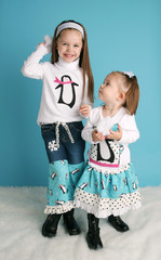 Cute toddler girls modeling winter penguin outfits