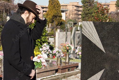 Mourning Man Standing on a Grave at the Cemetery