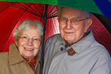aged couple with umbrella poster