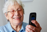 aged woman smiling at the screen of a cell phone poster