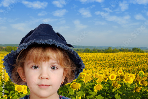 little girl portrait with sunflower field behind