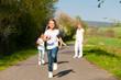 Kinder rennen auf Weg, schwangere Mutter in Hintergrund