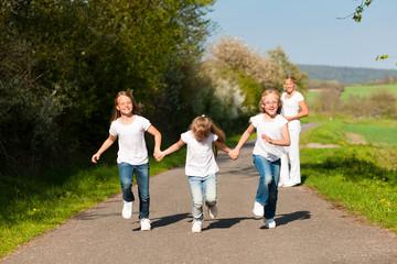 Kinder rennen auf Weg, Mutter in Hintergrund