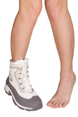 slender nude female legs in the winter tourist boots on a white