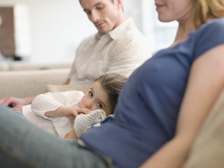 Girl Resting on Sofa Between Parents