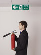 Businessman holding fire extinguisher under exit sign