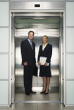 Smiling Businessman and Businesswoman in Office Elevator, portrait