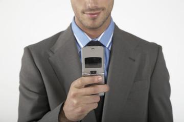 Businessman using mobile phone, mid section