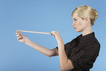 Businesswoman shooting rubber band, on blue background
