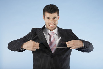 Businessman stretching rubber band, on blue background, portrait