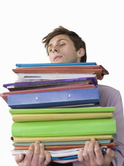 Male office worker carrying heavy binders, close-up