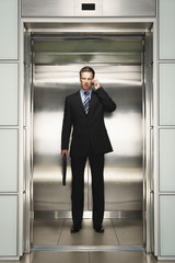 Businessman Using Cell Phone on Elevator, front view