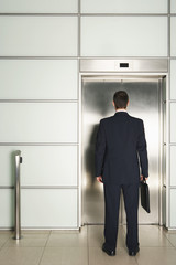 Businessman Waiting for Elevator, rear view