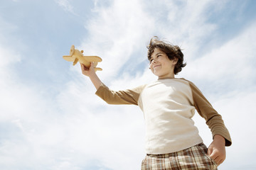Low angle view of boy holding up wooden toy airplane against blue sky