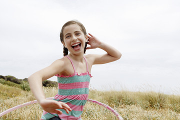 Smiling, pre-teen Girl Hula Hooping in field