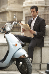 Man sitting by scooter, reading newspaper.