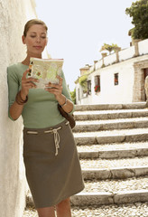 Tourist standing on steps reading map in Granada, Spain, front view