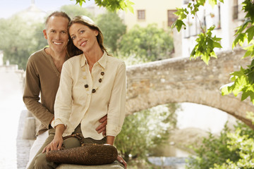 Tourist Couple sitting on wall by Stone Bridge, Granada, Spain, portrait