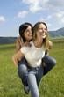 Young woman giving friend piggyback in mountain field, half length